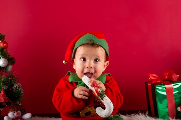 Милый годовалый мальчик в костюме эльфа сидит, держа во рту типичную рождественскую палку