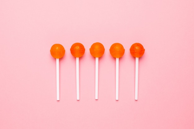 Sweet orange candy lollipop on pastel pink. minimalist composition.