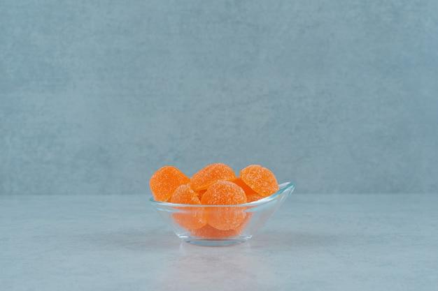 白い背景の上のガラスプレートに砂糖と甘いオレンジ色のゼリーキャンディー。高品質の写真