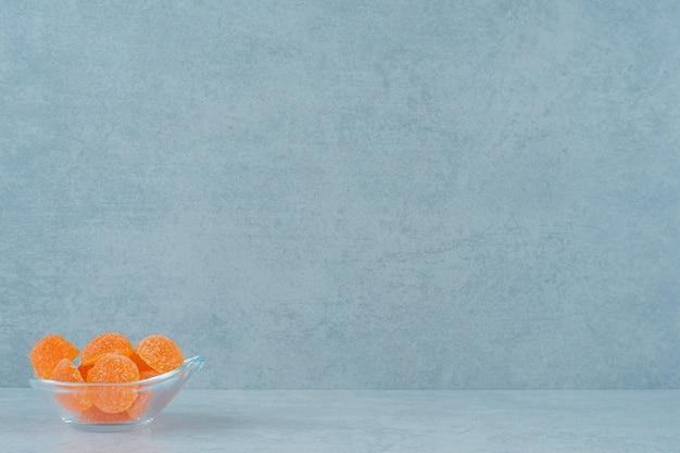 Сладкие апельсиновые желейные конфеты с сахаром в стеклянной тарелке на белой поверхности
