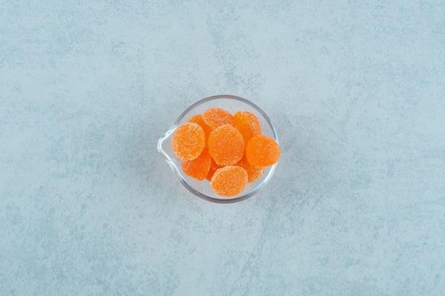 白い表面のガラスプレートに砂糖入りの甘いオレンジ色のゼリーキャンディー