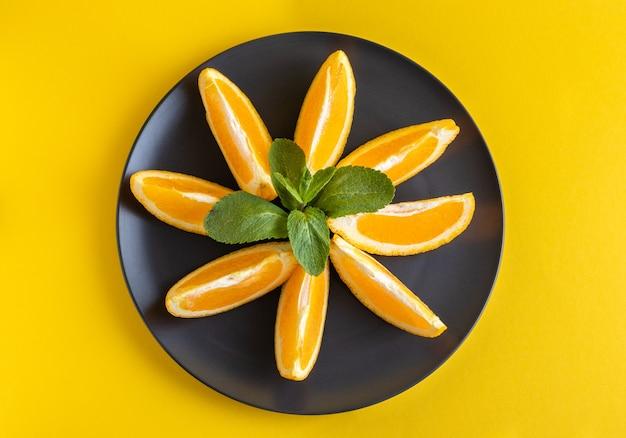 黄色の背景に置かれた暗い皿にミントの葉と甘いオレンジ スライス