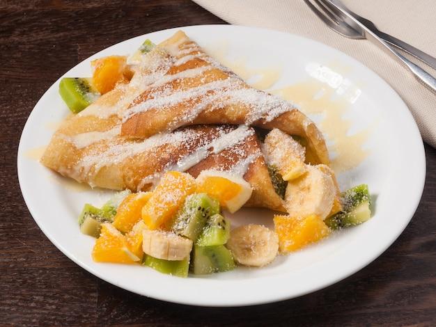 Сладкий блин с фруктами апельсин банан киви и сгущенкой