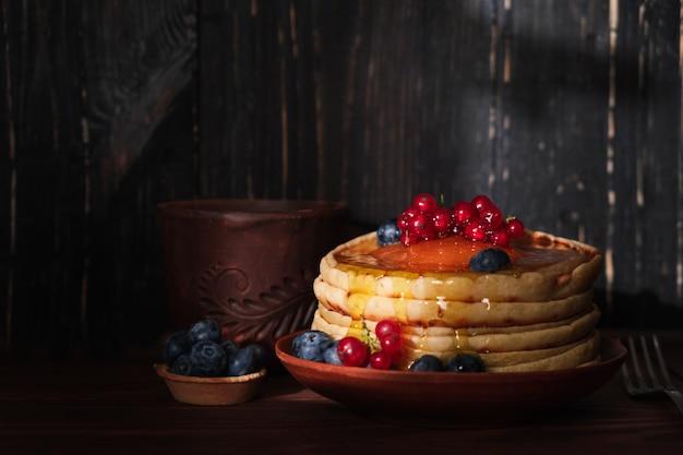 달콤한 팬케이크 블루 베리와 레드 커런트 토핑. 딸기와 코코넛 플레이크를 곁들인 홈 메이드 팬케이크