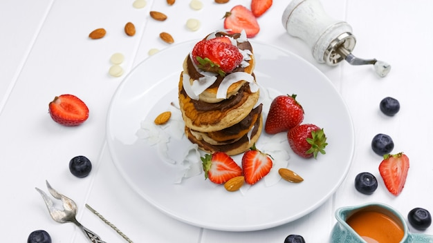 Sweet pancakes chocolate strawberry top view white background