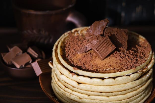 甘いパンケーキチョコレートトッピング。チョコレートの朝食と自家製のパンケーキ。皿の上の朝のデザートココアパンケーキ