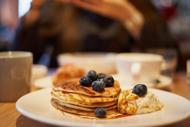 카페에서 접시에 카라멜 시럽 블루베리와 아이스크림을 곁들인 달콤한 팬케이크