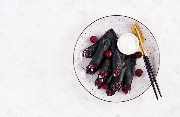 リコッタチーズとチェリーの甘いパンケーキ。黒のパンケーキ。朝ごはん。上面図、コピースペース