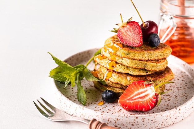 Sweet pancakes with spinach, drenched in honey, with fresh strawberries