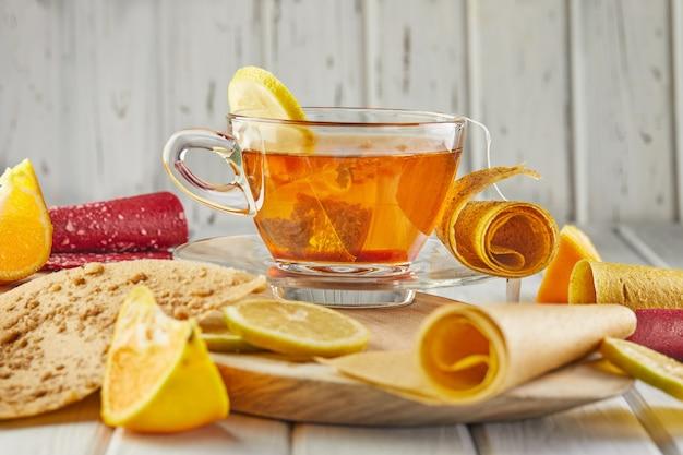 감귤류 과일과 레몬 차를 곁들인 순수한 과일의 달콤한 향. 건강한 과자-막대 사탕, 과일 칩. 열매와 과일의 천연 과자. 비타민과 비건 채식 식단.