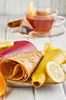 감귤류 과일과 레몬 차를 곁들인 순수한 과일의 달콤한 향. 건강한 과자-막대 사탕, 과일 칩.