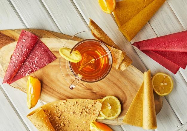 Сладкая пастила из чистых фруктов в рулетах с цитрусовыми и чаем с лимоном. полезные сладости -