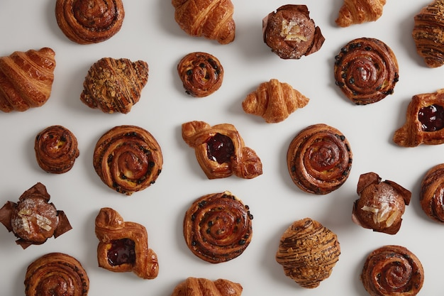 Pasticcini dolci, croissant, turbinii e cupcakes isolati su sfondo bianco, preparati con una ricetta speciale da farina, zucchero, pronti per la vendita in pasticceria. deliziosa pasticceria. concetto di cibo spazzatura