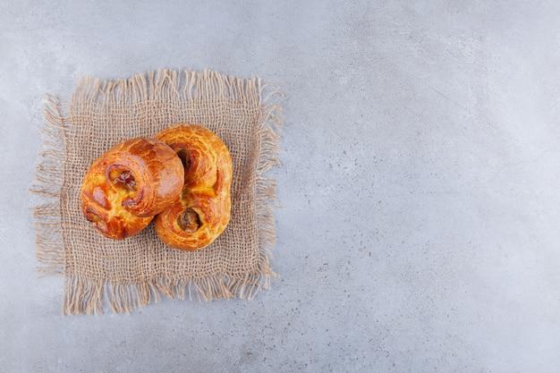 Pasticcini dolci adagiati su un piano di tela di sacco.