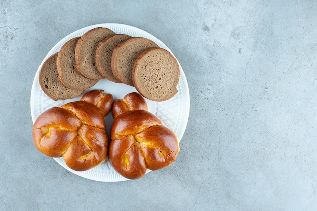Sweet pastry and bread slices on white plate.