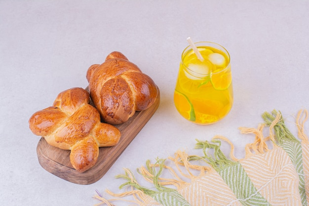 Sweet pastry buns on wooden platter with a glass of lemonade.