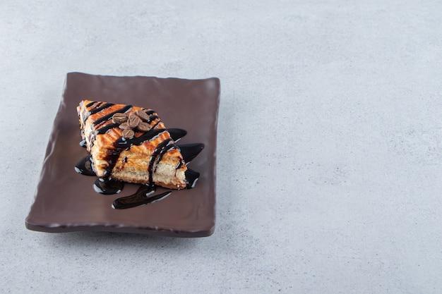 Pasta dolce decorata con cioccolato disposta sul piatto scuro. foto di alta qualità