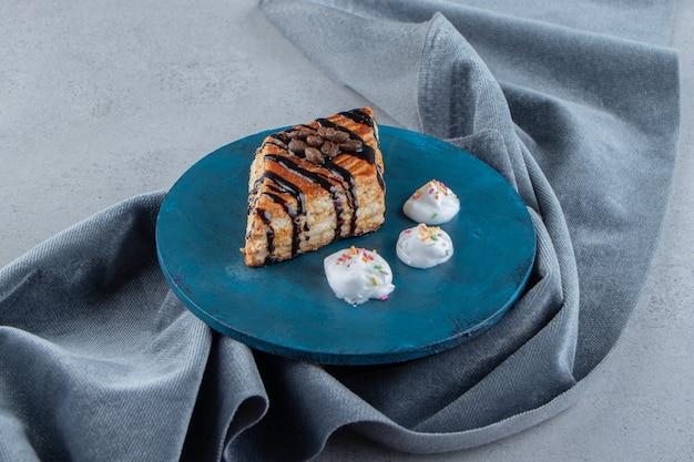 青い板の上に置かれたチョコレートで飾られた甘いペストリー。高品質の写真