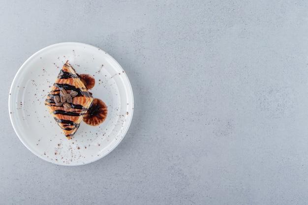 白い皿の上に置かれたチョコレートで飾られた甘いペストリー。高品質の写真