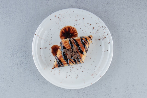 Sweet pastry decorated with chocolate placed on white plate