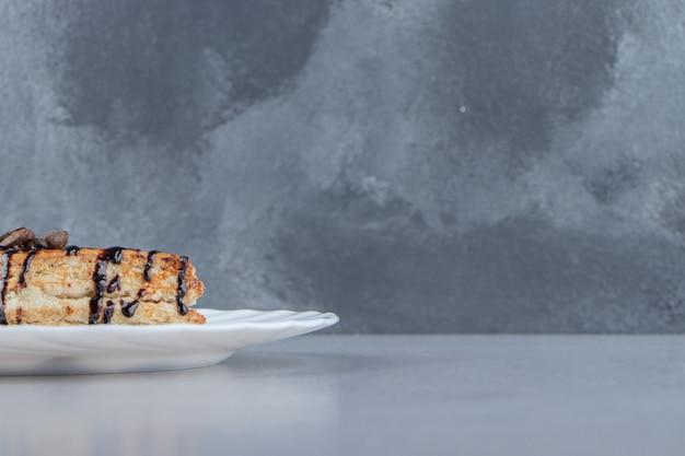 白い皿の上にチョコレートシロップで飾られた甘いペストリー。高品質の写真
