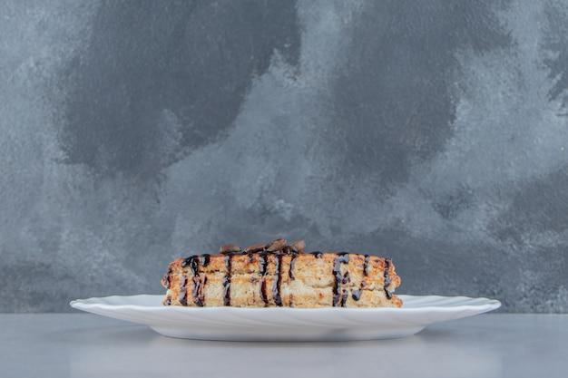 하얀 접시에 초콜릿 시럽으로 장식된 달콤한 패스트리