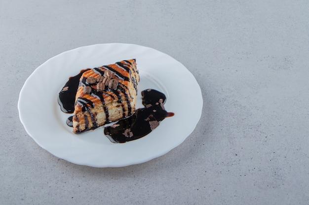 Pasta dolce decorata con sciroppo di cioccolato posto su piatto bianco. foto di alta qualità
