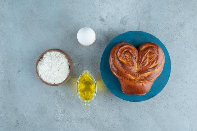 Сладкое тесто, мука и оливковое масло на мраморной поверхности.
