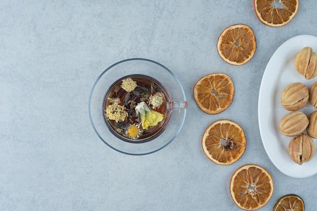 大理石の背景にドライオレンジとハーブティーのカップと甘いペストリー。高品質の写真