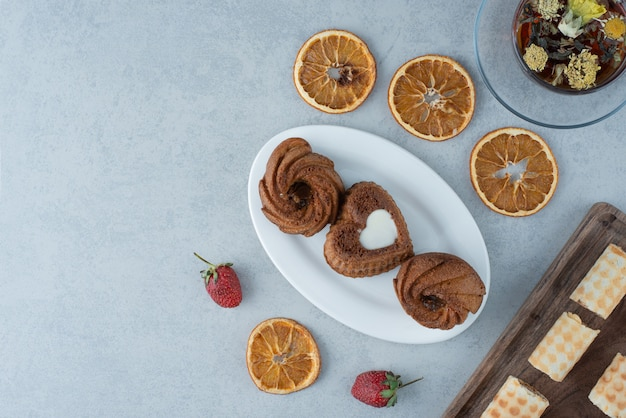 Sweet pastry with dried orange and cup of herbal tea on marble background. high quality photo