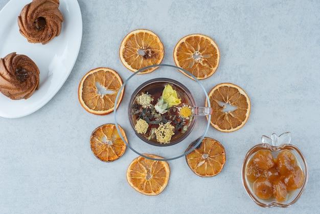 Pasta dolce con arancia secca e tazza di tisana su sfondo marmo. foto di alta qualità