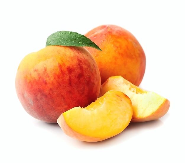 Сладкий персик приносит крупный план на белом.