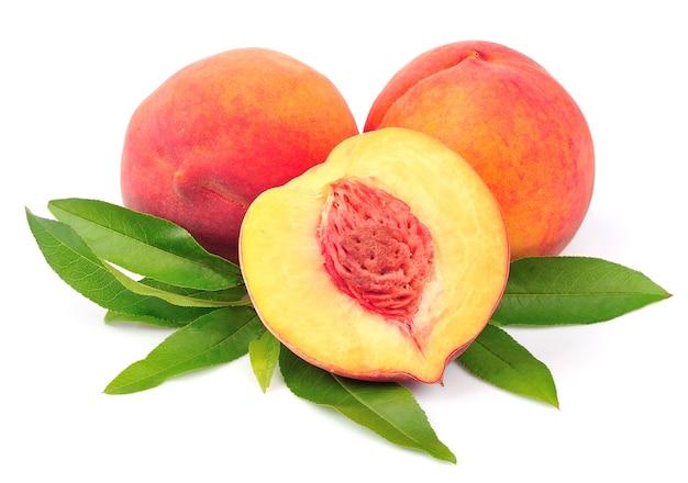 Сладкий персик с листьями крупным планом на белом