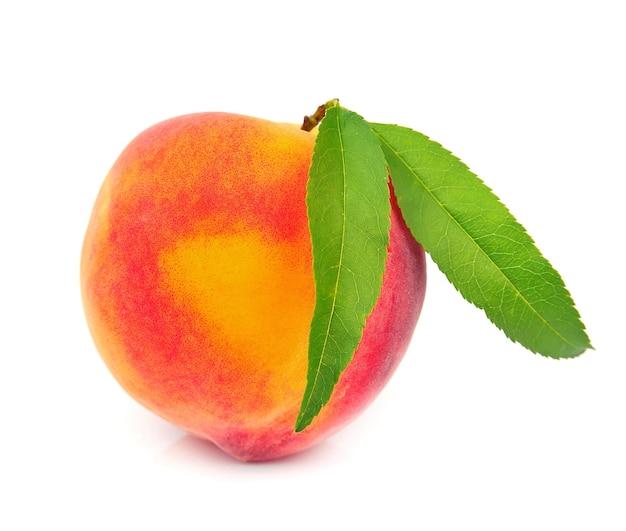 Сладкий персик с листьями на белом фоне