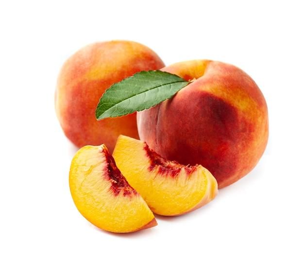 Сладкий персик с листьями на белом фоне.