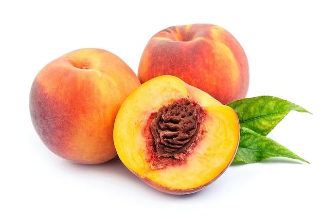 Сладкий персик с листьями на белом