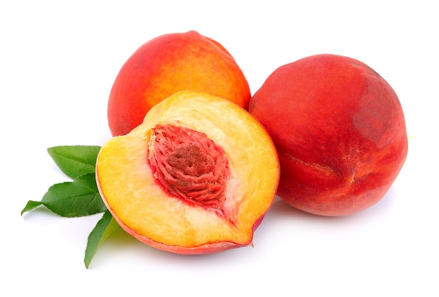 Сладкие персики с листьями на белом фоне Premium Фотографии