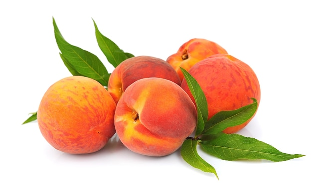 Сладкие персики с листьями на белом фоне