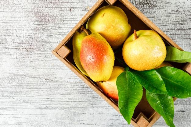 汚れた灰色の背景に平らな葉と木製の箱で甘い梨を置く