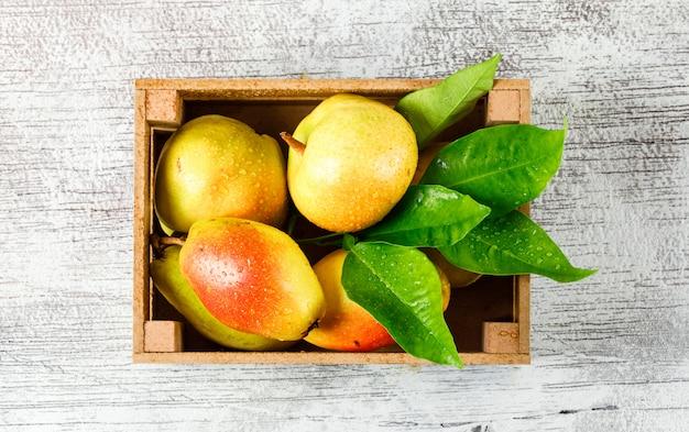 汚れた灰色の背景上の木製の箱の葉と甘い梨