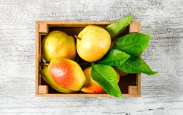 Sweet pears with leaves in a wooden box on grungy grey background