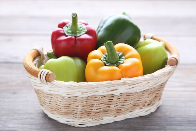 Sweet pepper in a basket on a grey background.