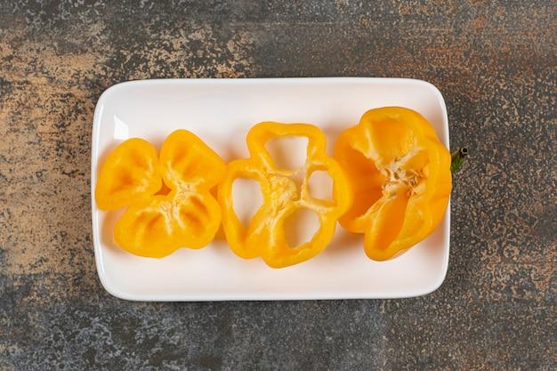 Сладкий перец в тарелке на мраморной поверхности