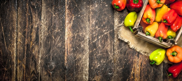 Sweet pepper in an old box. on a wooden background.