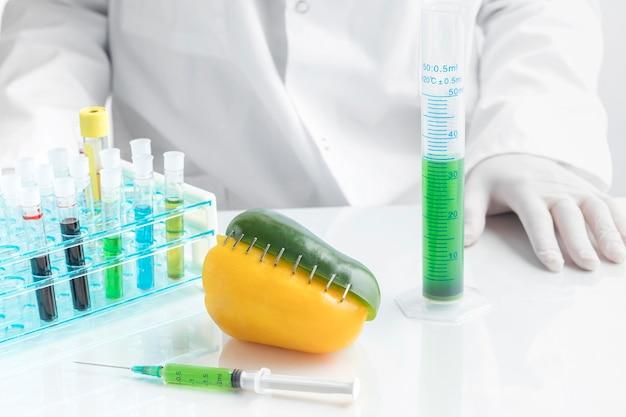 化学薬品で満たされた注射器で机の上のピーマン