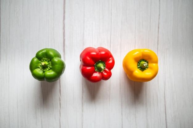 ピーマン、赤、緑、黄色のパプリカ、木製の背景に。
