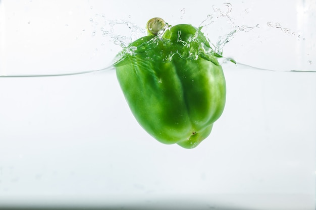 Sweet pepper in water splashes, green sweet pepper on white
