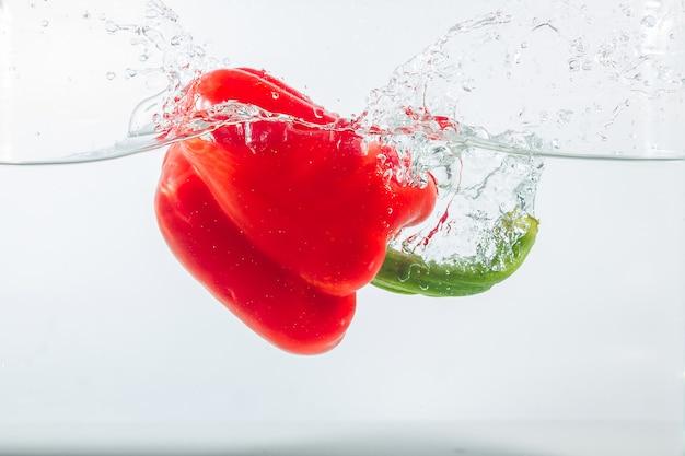 Sweet pepper in water splashes, red sweet pepper on white