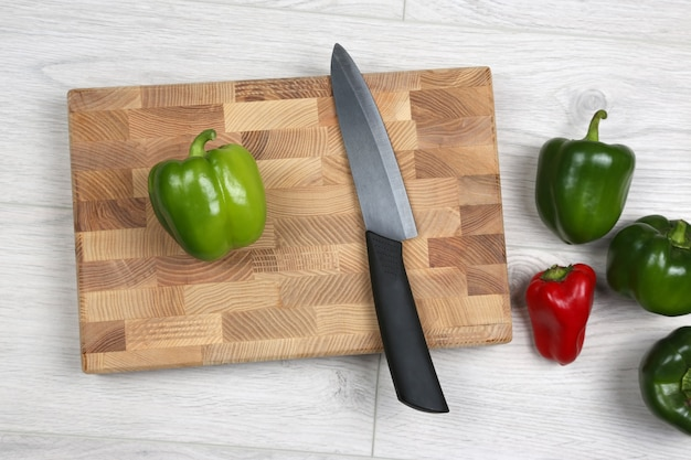 Sweet peppers with a ceramic knife on a wooden board