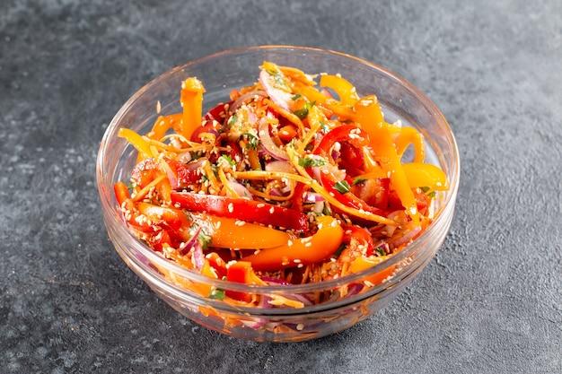 暗い背景のボウルに韓国のニンジン、ゴマ、野菜とピーマン。スパイシーな健康食品